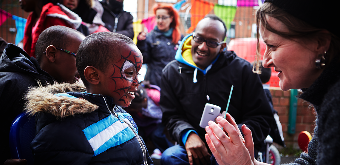 Boy has his face painted at community event